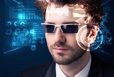 Ung man som ser med futuristiska smarta tekniskt avancerade exponeringsglas Arkivfoto