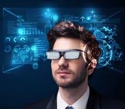Ung man som ser med futuristiska smarta tekniskt avancerade exponeringsglas Royaltyfria Foton