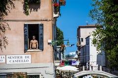 Ung man som ser till och med ett fönster i Venedig, Italien Royaltyfria Bilder