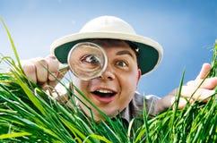 Ung man som ser till och med ett förstoringsglas Arkivbild