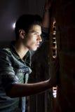 Ung man som ser till och med hålet i tegelstenvägg Royaltyfri Fotografi