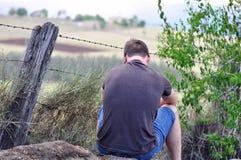 Ung man som sitter ensamt det friaandasökande Royaltyfri Foto