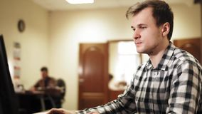 Ung man som sitter i kontoret och att arbeta på en dator och ett samtal arkivfilmer