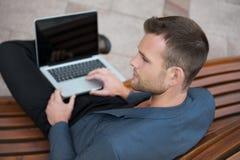 Ung man som sitter med hans bärbar dator Arkivfoton