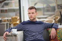 Ung man som sitter med hans kaffe Royaltyfria Foton
