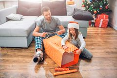 Ung man som sitter på golv med den lilla flickan och den packande stora asken av gåva De koncentreras på arbete Flickasnittdel arkivbild