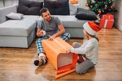 Ung man som sitter på golv med hans dotter och packande presemt Han rymmer bandet i händer och blickar på henne Grabbleenden royaltyfria bilder