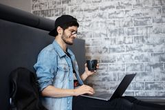 Ung man som sitter p? golvet med hans b?rbar dator p? hans varvar som dricker kaffe royaltyfri foto