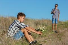 Ung man som sitter vid vägen med blommor som väntar på andra, begreppet av förhållandet arkivbilder