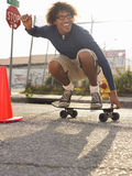 Ung man som Skateboarding på den stads- gatan Arkivfoton