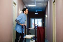 Ung man som skjuter en hushållningvagn laden med rena handdukar, tvätteri och gör ren utrustning i ett hotell, som han servar Royaltyfri Fotografi