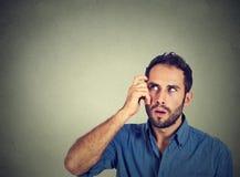 Ung man som skrapar huvudet som djupt tänker om något arkivfoton
