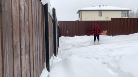 Ung man som skyfflar snö nära huset arkivfilmer