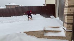 Ung man som skyfflar snö nära huset stock video