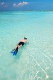Ung man som snorkling i den tropiska lagun med over vattenbungalower Royaltyfri Bild
