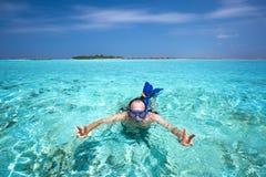 Ung man som snorkling i den tropiska lagun med over vattenbungalower royaltyfri fotografi