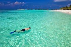 Ung man som snorkling i den tropiska lagun med over vattenbungalower, Maldiverna Royaltyfria Bilder