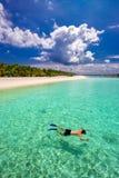 Ung man som snorkling i den tropiska lagun med over vattenbungalower, Maldiverna Royaltyfri Bild