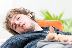 Ung man som sover med hans hund på hans bröstkorg Royaltyfri Foto