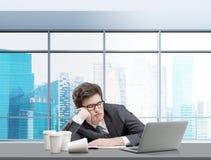 Ung man som sover på arbetsplatsen Arkivfoton