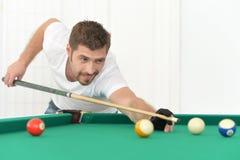 Ung man som spelar billiard Arkivfoto