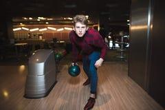 Ung man som spelar bowling med en blå boll för att bowla En man kastar en kula på en pinne Royaltyfri Fotografi