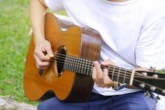ung man som spelar den akustiska gitarren i trädgården arkivbild