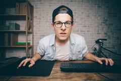 Ung man som spelar den modiga hemmastadda och strömmande playthrough- eller walkthroughvideoen Arkivfoton