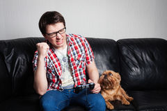 Ung man som spelar den modiga hemmastadda playthrough- eller walkthroughvideoen Den attraktiva mannen bär glasögon Han är lycklig Royaltyfri Foto