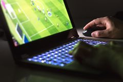 Ung man som spelar fotboll- eller fotbollleken direktanslutet med bärbara datorn arkivfoto