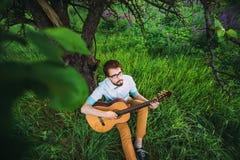 Ung man som spelar gitarren som är utomhus- under trädet arkivfoton