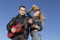 Ung man som spelar gitarren med kvinnan som är dansa och ta av hennes hatt Arkivbild