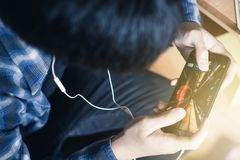 Ung man som spelar lekar på den smarta telefonen royaltyfri foto