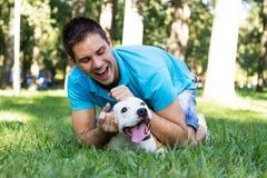 Ung man som spelar med hans hund Royaltyfri Foto