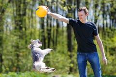 Ung man som spelar med hans hund Royaltyfri Fotografi