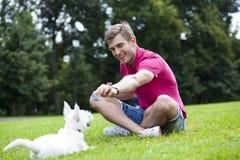 Ung man som spelar med hans hund i parkera Royaltyfri Foto