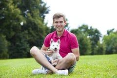 Ung man som spelar med hans hund i parkera Arkivfoton