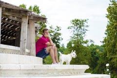 Ung man som spelar med hans hund i parkera Royaltyfria Foton