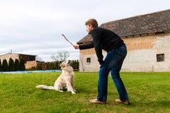 Ung man som spelar med hans hund i trädgård Royaltyfri Fotografi