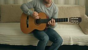 Ung man som spelar på den akustiska gitarren stock video