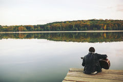 Ung man som spelar på gitarren på sjön royaltyfri fotografi