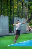 Ung man som spelar tennis på en solig dag arkivfoton