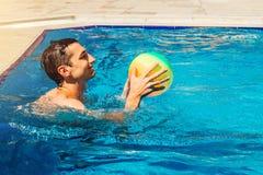 Ung man som spelar vattenpolo i simbassäng konkurrensar som dyker pölsportar som simmar vatten sund livsstil för begrepp Sommarak Royaltyfria Foton