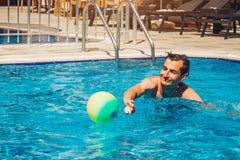 Ung man som spelar vattenpolo i simbassäng konkurrensar som dyker pölsportar som simmar vatten sund livsstil för begrepp Arkivfoton
