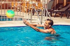 Ung man som spelar vattenpolo i simbassäng konkurrensar som dyker pölsportar som simmar vatten sund livsstil för begrepp Fotografering för Bildbyråer