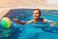 Ung man som spelar vattenpolo i simbassäng konkurrensar som dyker pölsportar som simmar vatten sund livsstil för begrepp Sommarun Royaltyfri Bild