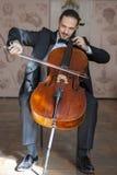 Ung man som spelar violoncellen Stående av cellisten arkivfoto