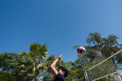 Ung man som spelar volleyboll utomhus royaltyfria bilder