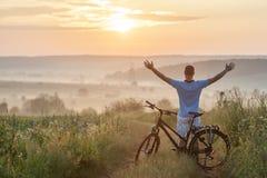 Ung man som står nära cykeln i morgonsoluppgång med wonderf arkivfoto