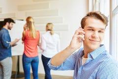 Ung man som studenten som kallar med smartphonen Royaltyfri Bild